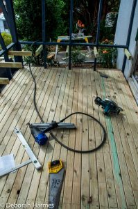 Deck being installed prior to walls going up on timber-slatted screen porch.