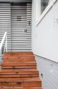 Entry stairs up to bespoke timber-slatted screen porch on front of Mid Century ranch house.