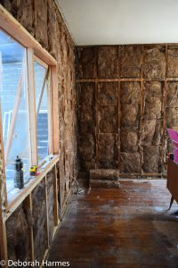 Livingroom (lounge room) walls filled with thick batts of insulation & new timber double-glazed windows.