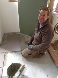Mark installing ceramic tile floor in the back hallway and adjoining laundry room.
